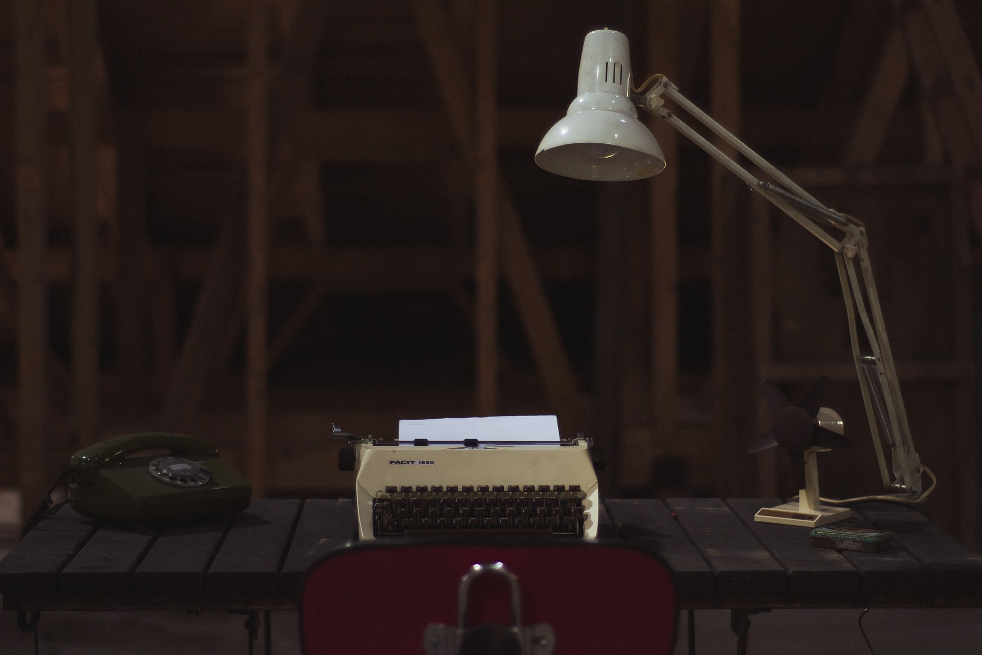 a typewriter on a table with a lamp overhead